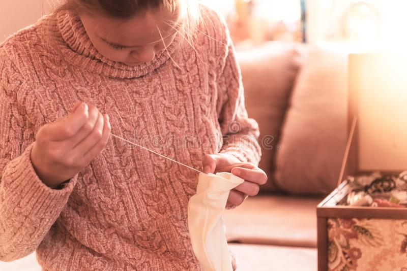 Young girl sews a button to her blouse stock image