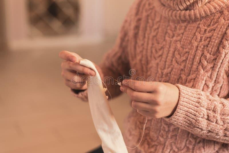 Young girl sews a button to her blouse stock photos