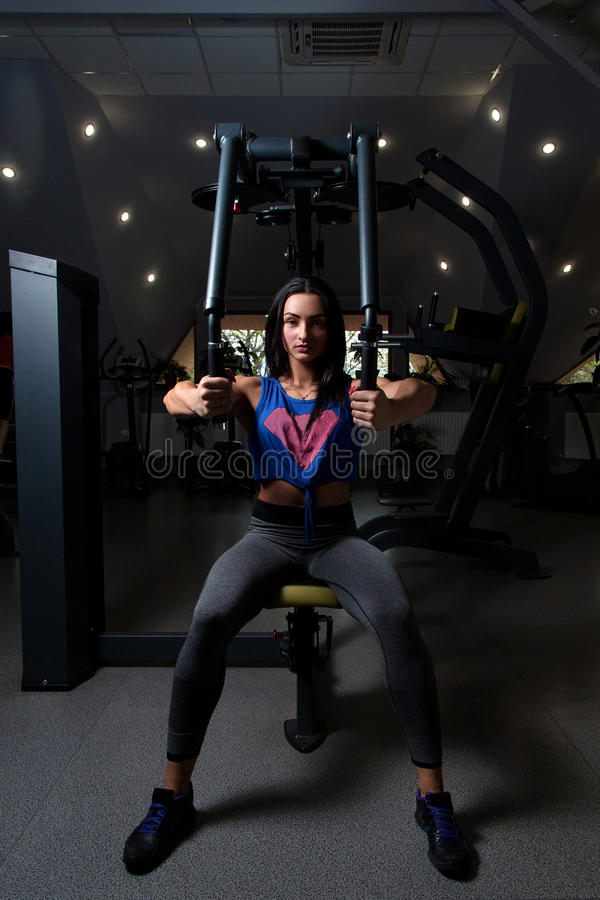 young girl with sexual inflated figure, in the gym doing exercise on the chest royalty free stock image
