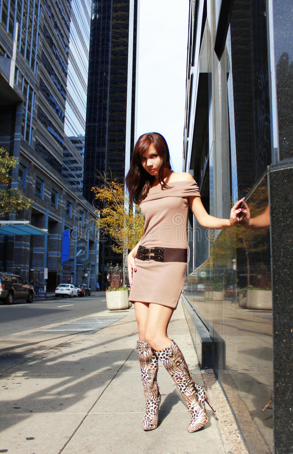 Young girl in boots posing in a city stock image
