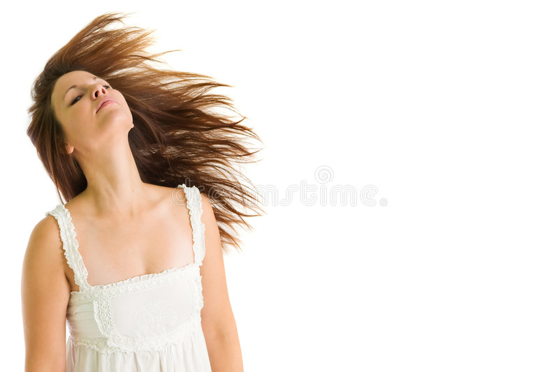 Young girl shaking her head. Young attractive girl in white dress shaking her head with hair on the move against white background royalty free stock photos