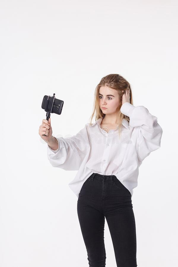 Happy young girl making self portrait with smartphone attached to small tripod royalty free stock image