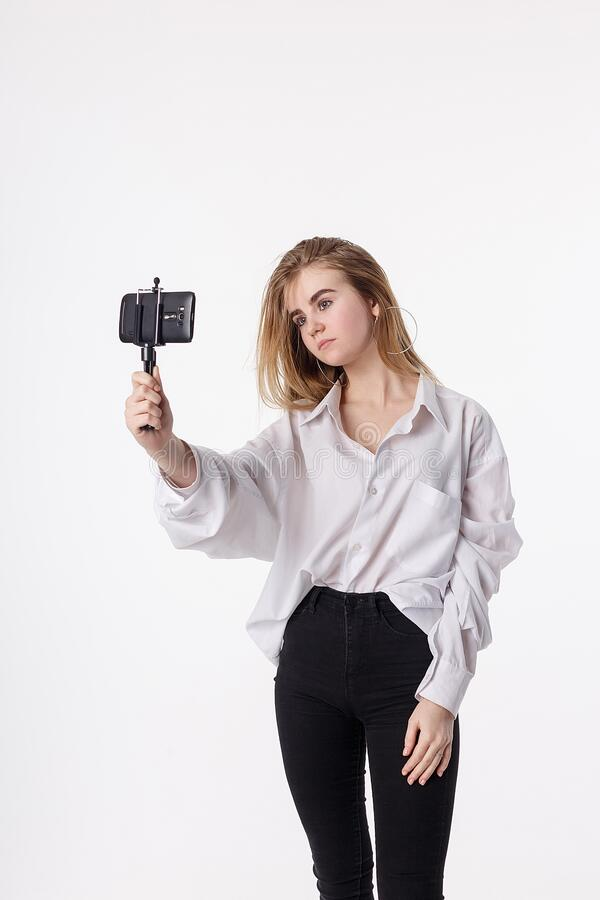 Young pretty girl making self portrait with smartphone attached to small tripod royalty free stock image