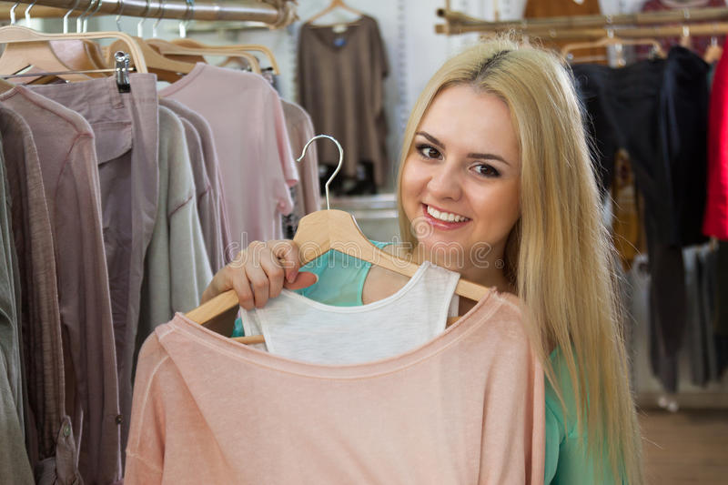 Young girl shopping jersey. Happy young girl shopping jersey at the apparel store royalty free stock photos