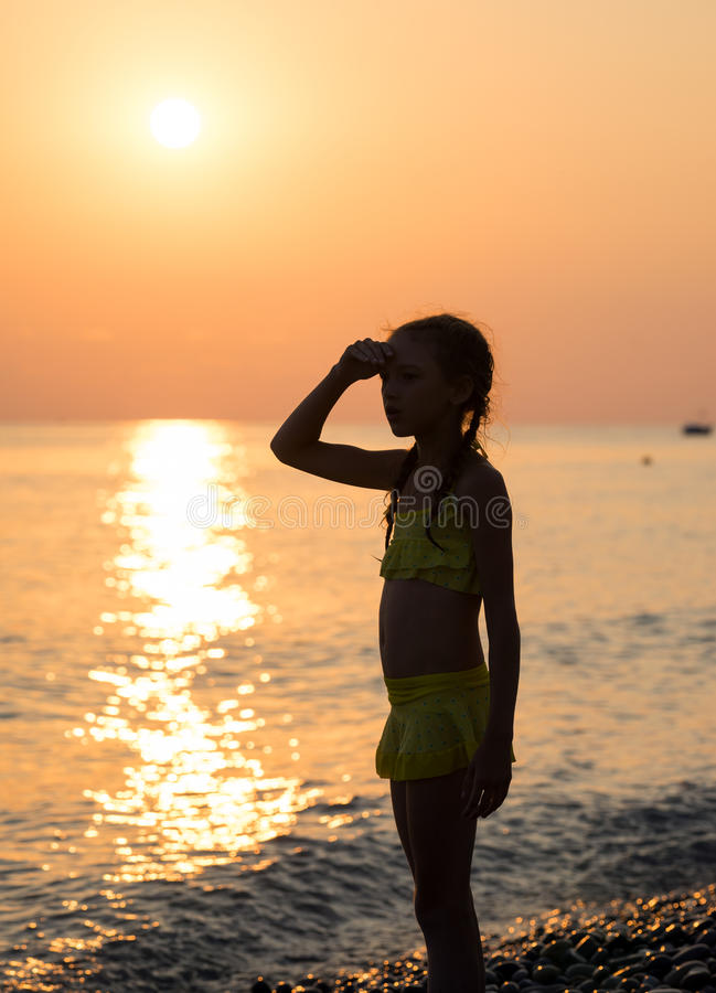 Young girl on shore sea. Young girl stand on shore sea and looking off into the distance with his hand raised to his forehead at sunset. Beautiful landscape stock photography