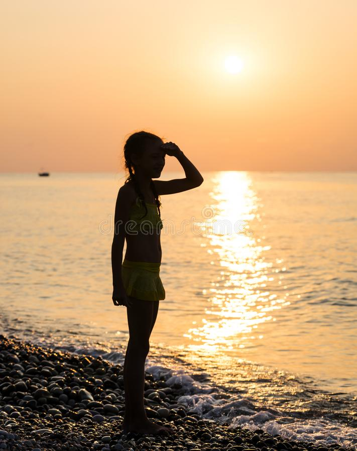 Young girl on shore sea. Young girl stand on shore sea and looking off into the distance with his hand raised to his forehead at sunset. Beautiful landscape stock photos