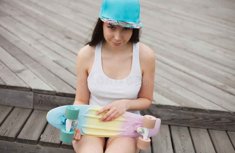 Young girl with short cruiser skateboard deck outdoors royalty free stock photography