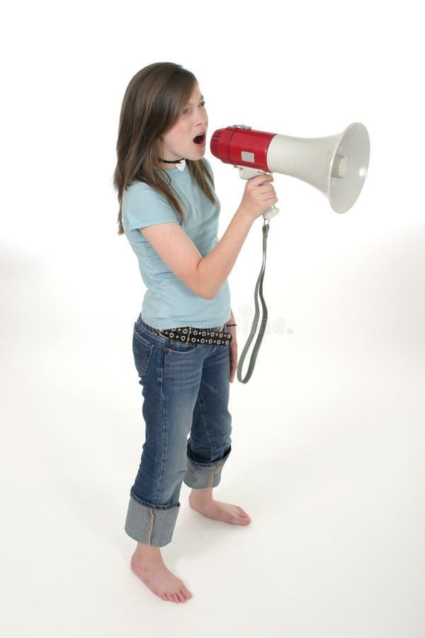 Young Girl Shouting Through Megaphone 3. Young child or tween girl shouting, speaking, or singing through a megaphone. Shot on white royalty free stock image