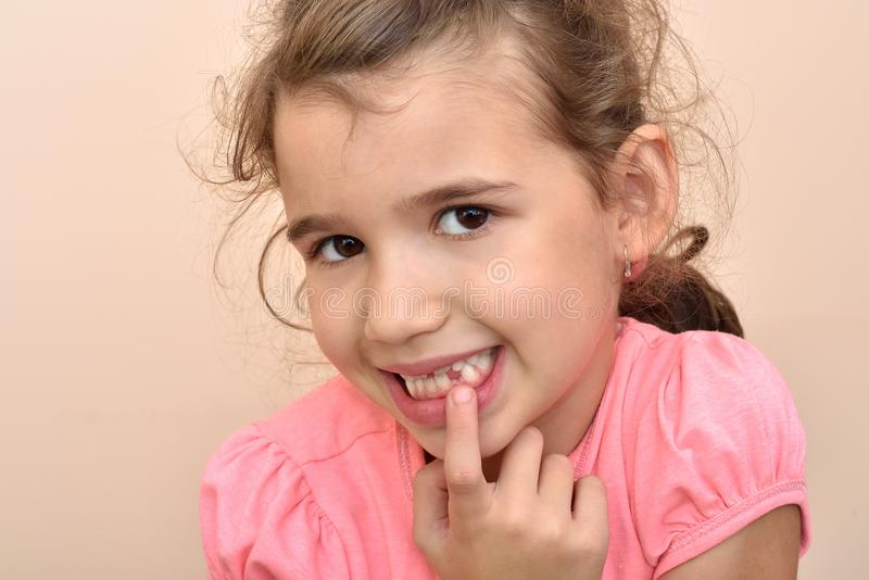 Young girl showing a missing tooth. Cute young girl showing a missing tooth with her index finger stock photography