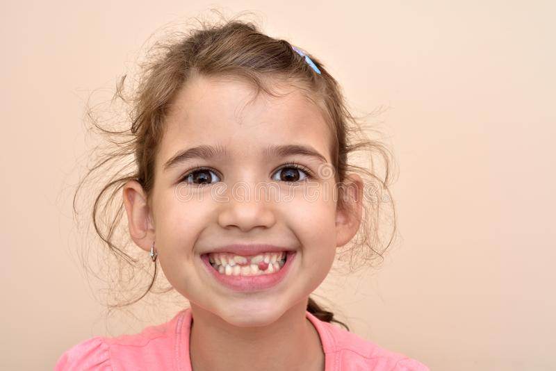 Young girl showing a missing tooth. Cute young girl showing a missing tooth royalty free stock photos