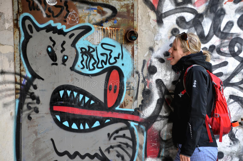 Young girl shows her tongue with wall paintings (graffiti) in background stock photography