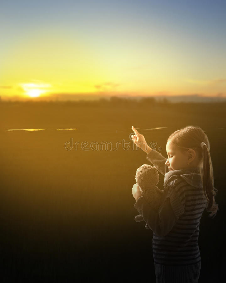 The young girl shows the plush toy at sunset. royalty free stock photos