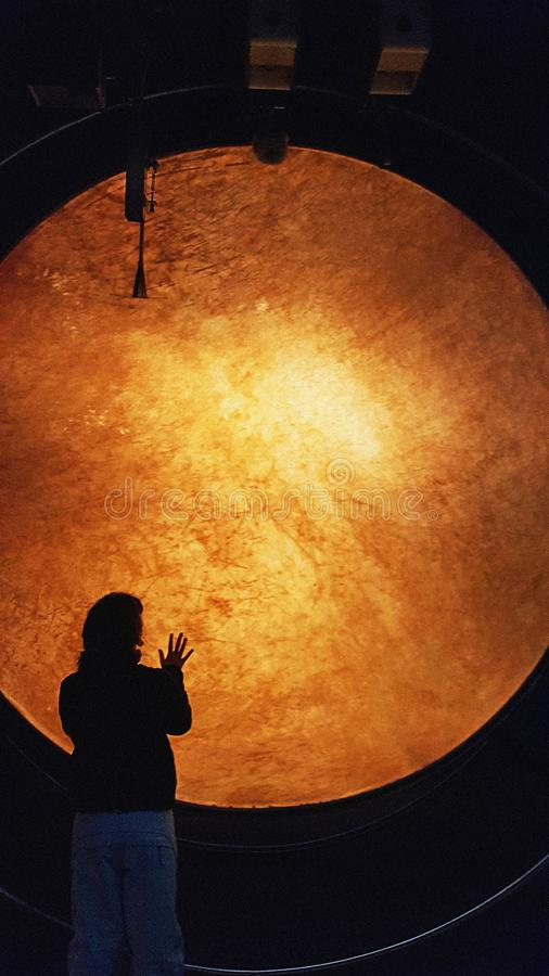A young girl silhouette in front of a giant drum lightened from background in music museum royalty free stock image