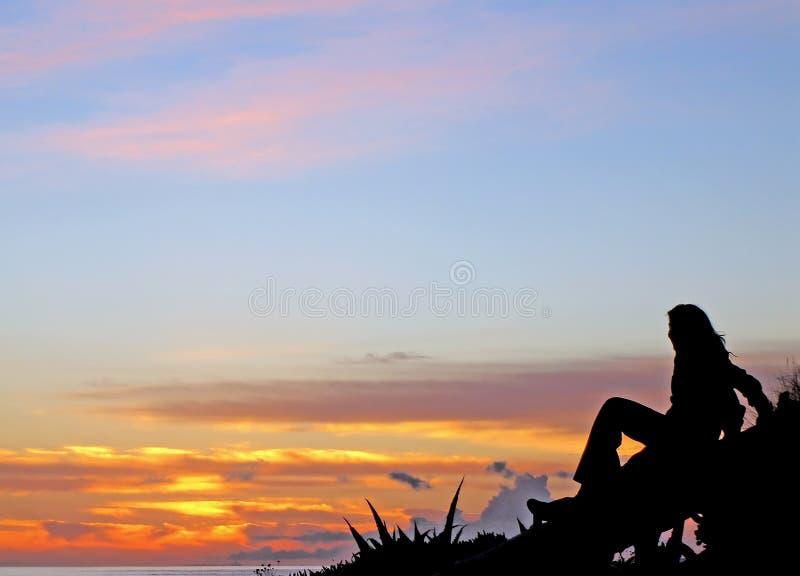 Young girl gazing the sunset beach stock photo