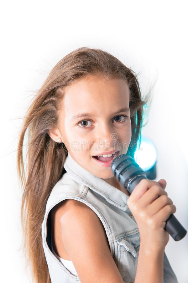 Young girl singing with microphone. Young girl with denim jacket singing while holding a microphone on a white background stock image