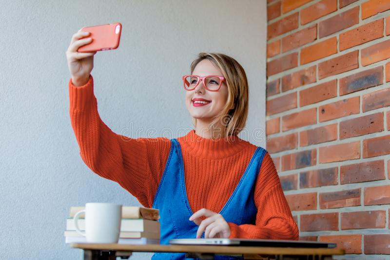 Girl sititng at table with computer and do a selfie royalty free stock photos