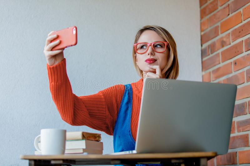Girl sititng at table with computer and do a selfie stock photos