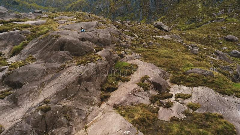 Young girl sits alone in the rocky mountains of Dingle Peninsula royalty free stock images