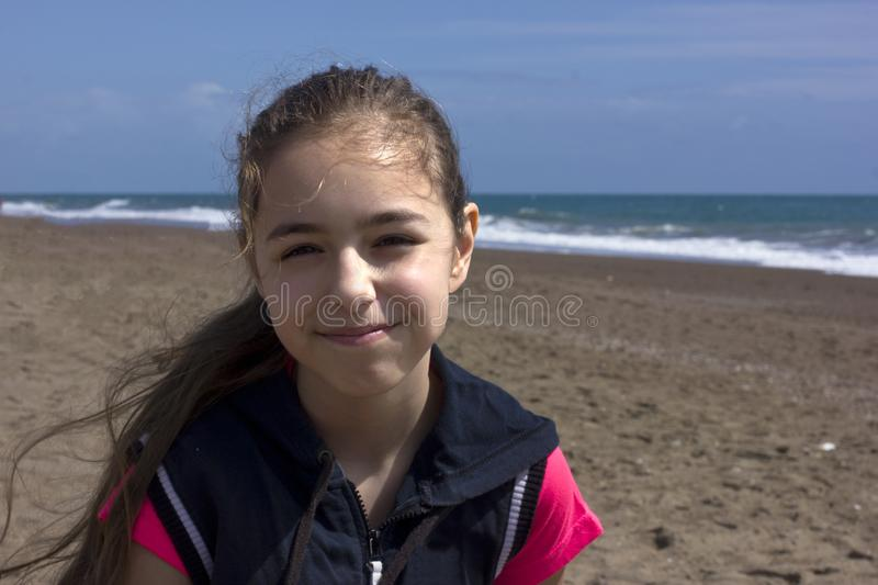 Young girl sits on the beach near the blue sea royalty free stock image