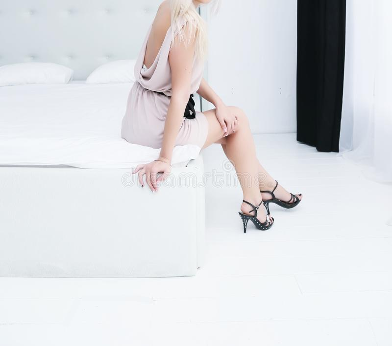 A Young Girl Sits In The Bedroom On The Bed In A White Dress And Heels, A  Young Girl Sits In The Bedroom On The Bed In A White Dress And Heels