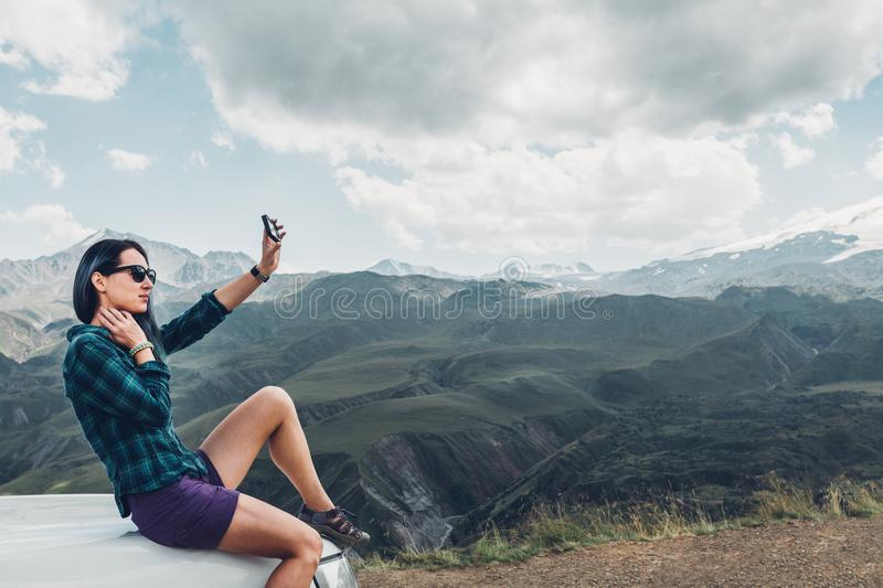 Young Girl Sits On Car And Makes Selfie On Smatrphone On Summer Mountain Background. Travel Discovery Journey Concept. A beautiful young girl in a shirt and royalty free stock photo