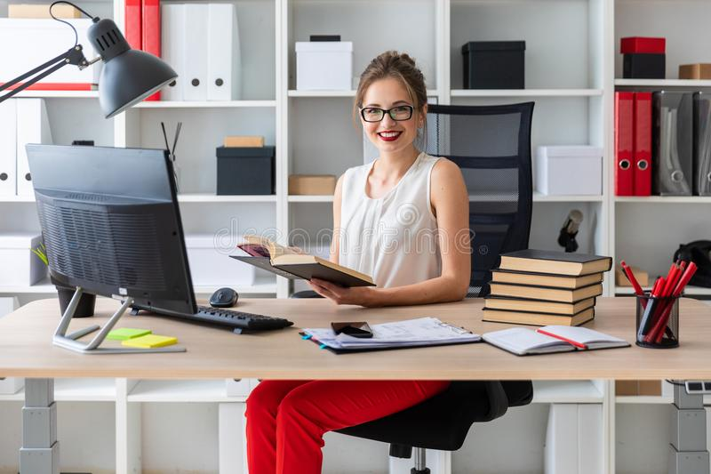 A young girl sits at a computer table and holds an open book in her hands. Beautiful young girl in glasses and a white blouse is working in the office. photo royalty free stock image