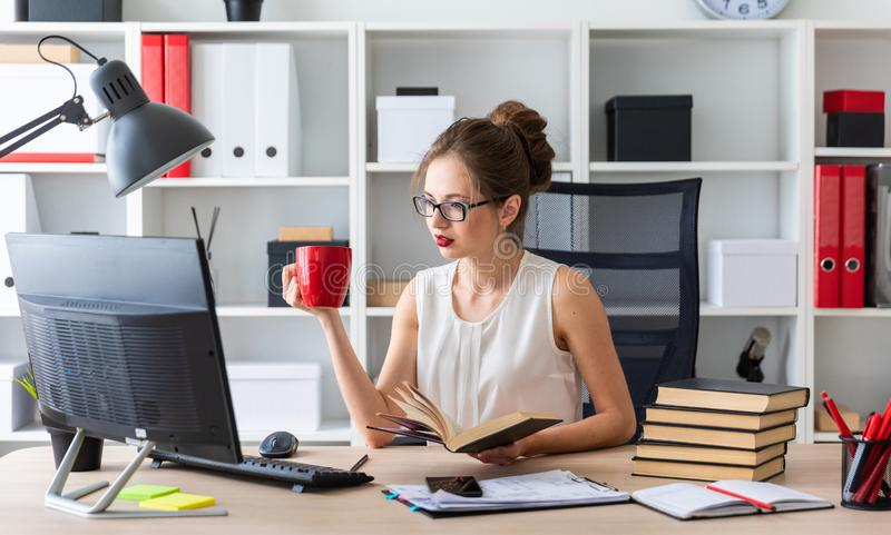A young girl sits at a computer table and holds an open book and a red cup in her hands. Beautiful young girl in glasses and a white blouse is working in the stock images