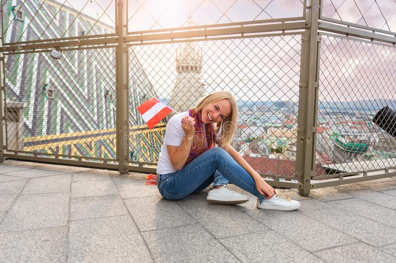 A young girl sits on the floor against the background of the panorama of Vienna and against the roof of St. Stephen`s royalty free stock photography