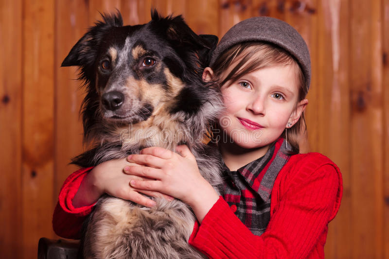 Young girl sits next to his friend dog breed Border Collie. On the farm. stock photo