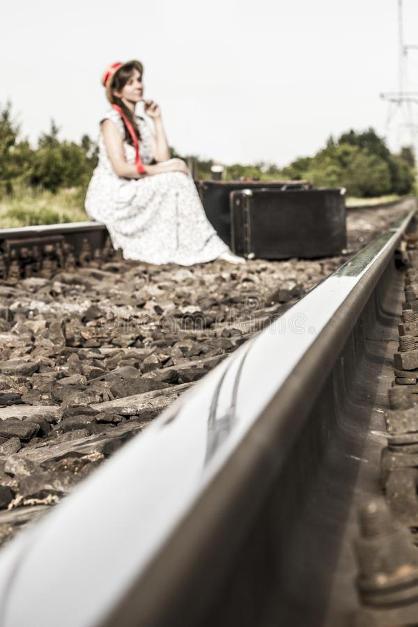 A young girl sits with a suitcase on the railway tracks. Beautiful girl is waiting with a suitcase.  teenager in a canapes hat wit stock photos