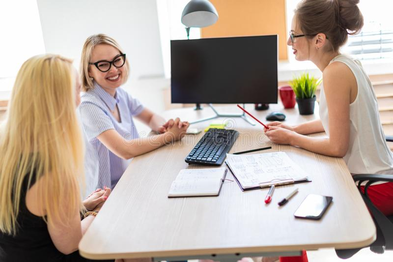 A young girl sits at a table in her office and talks to two co-partners. The girl is holding a pencil in her hand and. Beautiful young girl in glasses and a red stock images