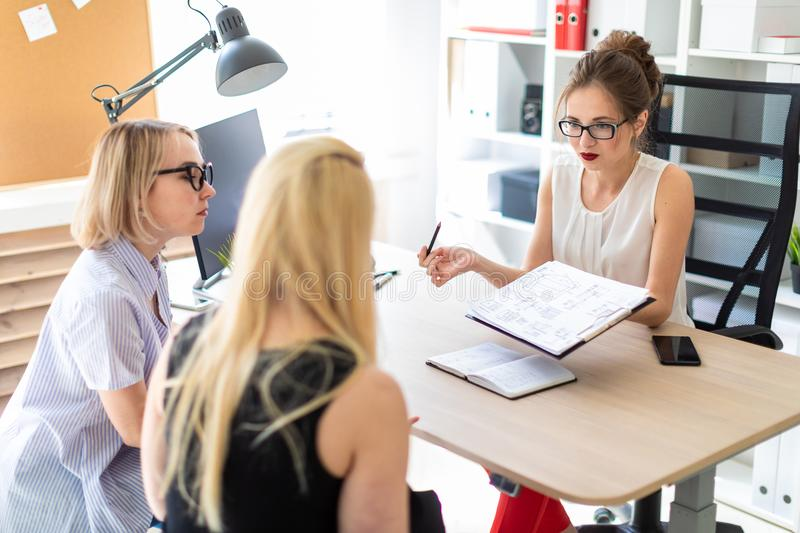 A young girl sits at a table in her office and talks to two co-partners. The girl is holding a pencil in her hand and. Beautiful young girl in glasses and a red royalty free stock images