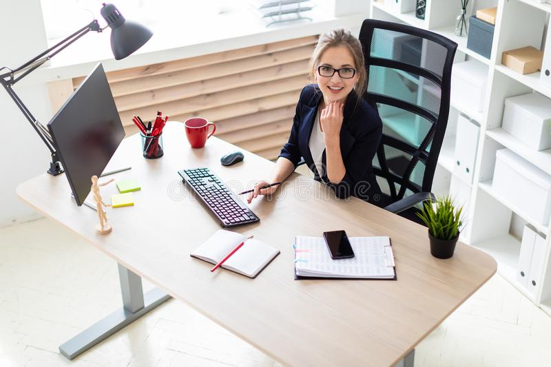 A young girl sits at a table and holds a pencil in her hand. A beautiful young girl with glasses, a white blouse and a jacket is working in her office. photo stock photos