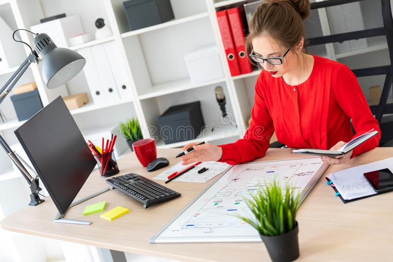 A young girl sits at a table in the office, holds a marker in her hand and works with a notepad and a magnetic board. Beautiful young girl in glasses and a red stock photos