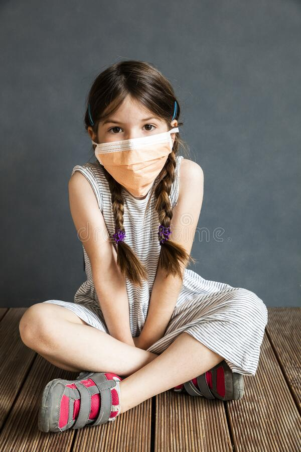 Young girl sitting wearing a protective mask stock image