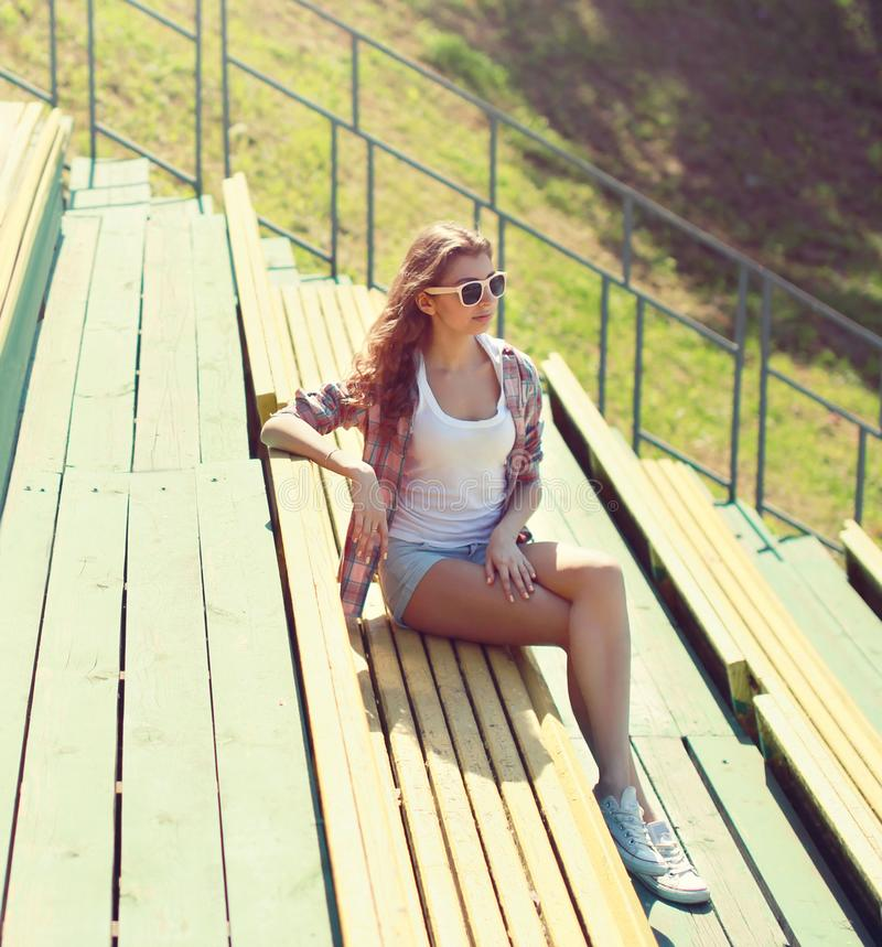 Young girl sitting on bench in city park on sunny summer royalty free stock photos