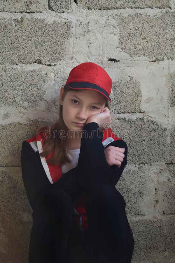 Young girl is sitting in black sports suit, red cap. Concept portrait of a sad teenager stock photo