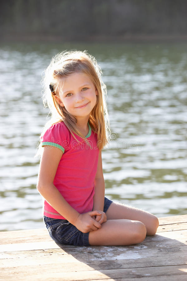 Free Young Girl Sitting By Lake Stock Photo - 21097930