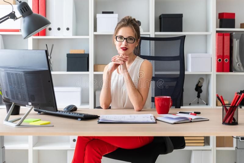 A young girl is sitting at the desk in the office. A young girl is sitting at the desk in the office royalty free stock photography