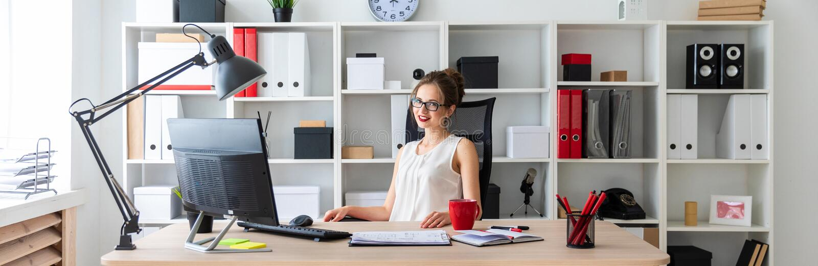 A young girl is sitting at the desk in the office. A young girl is sitting at the desk in the office stock image