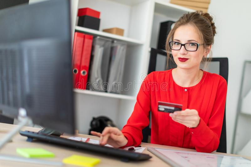 A young girl is sitting at the desk in the office, holding a bank card in her hand and typing on the keyboard. Beautiful young girl in glasses and a red shirt stock photography