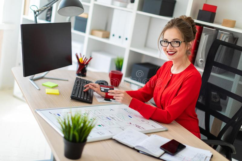 A young girl is sitting at the desk in the office, holding a bank card in her hand and typing on the keyboard. Beautiful young girl in glasses and a red shirt royalty free stock photo
