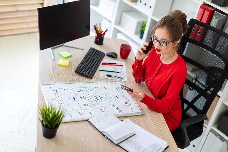 A young girl is sitting at the desk in the office, holding a bank card and phone in her hand. Beautiful young girl in glasses and a red shirt is working in the royalty free stock photo
