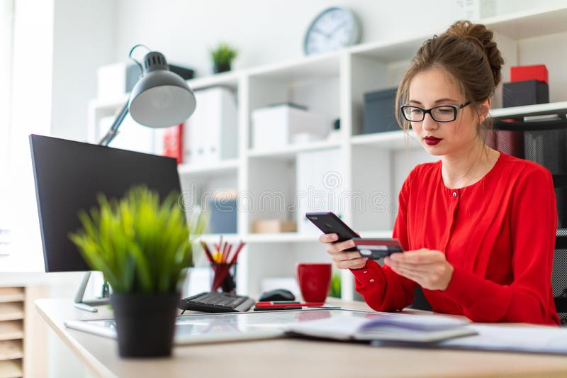 A young girl is sitting at the desk in the office, holding a bank card and phone in her hand. royalty free stock photography