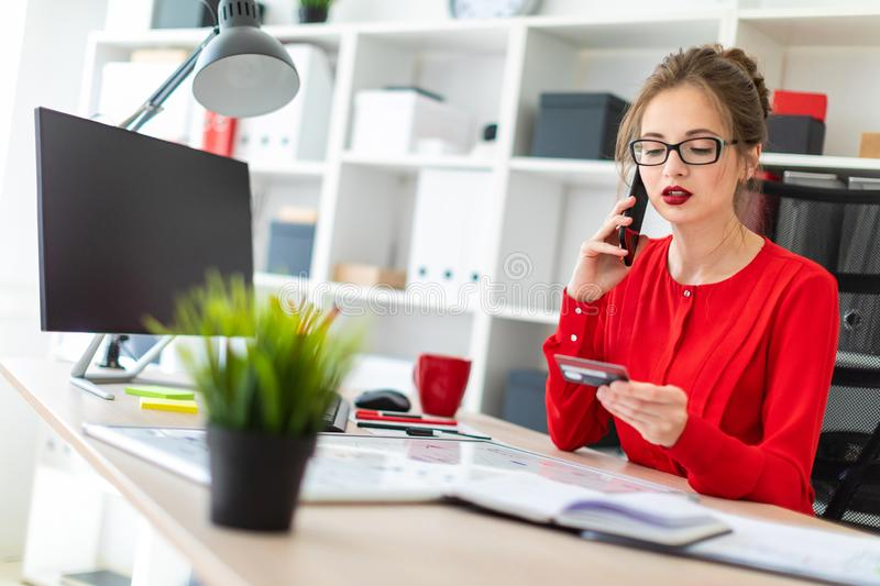 A young girl is sitting at the desk in the office, holding a bank card and phone in her hand. Beautiful young girl in glasses and a red shirt is working in the stock images