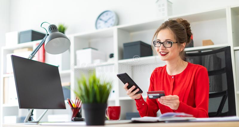 A young girl is sitting at the desk in the office, holding a bank card and phone in her hand. Beautiful young girl in glasses and a red shirt is working in the royalty free stock images