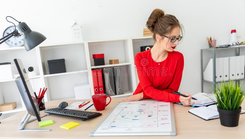 A young girl is sitting at the desk in the office, holding a black marker in her hand and working with a notepad. A. Beautiful young girl in glasses and a red royalty free stock images