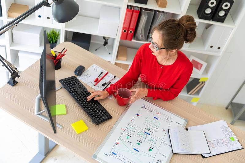 A young girl is sitting at the desk in the office, holding a red cup by her hand and typing on the keyboard. A magnetic stock photography