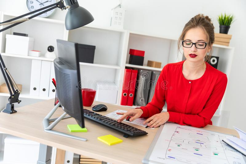 A young girl is sitting at the desk in the office and typing on the keyboard. A magnetic board lies before the girl. Beautiful young girl in glasses and a red royalty free stock image