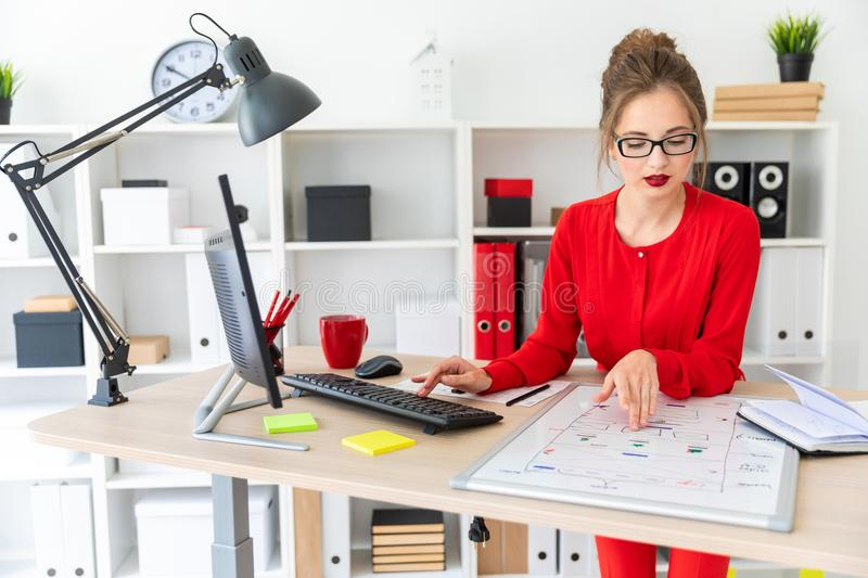 A young girl is sitting at the desk in the office and typing on the keyboard. A magnetic board lies before the girl. Beautiful young girl in glasses and a red stock image